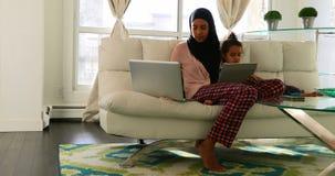 使用膝上型计算机和数字片剂的年轻母亲和女儿在客厅4k 股票视频
