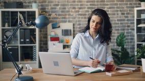 使用膝上型计算机和文字的年轻女人雇员在笔记本在书桌在办公室 股票录像