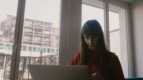 使用膝上型计算机和智能手机的愉快的确信的年轻白种人女实业家在大窗口在巴黎,通过的火车  股票视频