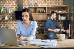 使用膝上型计算机和智能手机的年轻女实业家,当在家时工作 免版税图库摄影