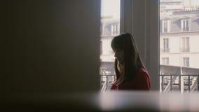 使用膝上型计算机和智能手机,在大公寓窗口的饮用的咖啡的美丽的轻松的年轻女实业家在巴黎 影视素材
