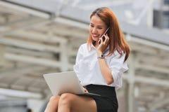 使用膝上型计算机和流动巧妙的电话的秀丽年轻亚裔女商人为工作在外部办公室 库存图片