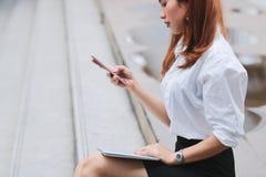 使用膝上型计算机和流动巧妙的电话的秀丽年轻亚裔女商人为工作在外部办公室 免版税库存照片
