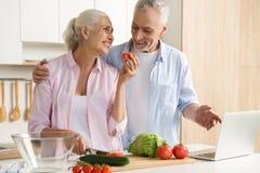 使用膝上型计算机和烹调的快乐的成熟爱恋的夫妇家庭 免版税库存照片