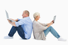 使用膝上型计算机和片剂个人计算机的成熟夫妇 免版税库存图片