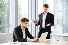 使用膝上型计算机和片剂的两个英俊的年轻商人在办公室 库存照片