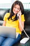 使用膝上型计算机和电话在长沙发的亚裔妇女 免版税库存照片