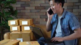使用膝上型计算机和电话的亚裔男性企业家有盒的箱子在家 股票录像
