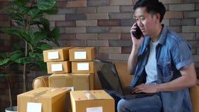使用膝上型计算机和电话的亚裔男性企业家有盒的箱子在家 影视素材
