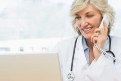 使用膝上型计算机和电话的女性医生在医疗办公室 库存照片