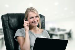 使用膝上型计算机和电话的年轻女商人在办公室 库存照片