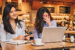 使用膝上型计算机和笑,两名年轻愉快的妇女在咖啡馆坐在桌上, 在桌纸笔记本上 免版税库存图片