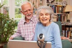 使用膝上型计算机和网络摄影的资深夫妇谈话与家庭 免版税库存照片