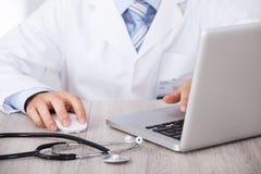 使用膝上型计算机和老鼠的医生的中央部位在书桌 免版税库存图片