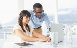 使用膝上型计算机和耳机的微笑的工友 库存照片