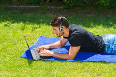 使用膝上型计算机和耳机的年轻人户外 免版税库存照片