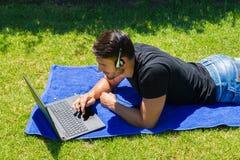 使用膝上型计算机和耳机的年轻人户外 图库摄影