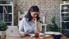 使用膝上型计算机和读书纸张文件的担心的经理运作在单独办公室 股票录像