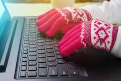 使用膝上型计算机在一个冷的冬天-有手套的女性 库存图片