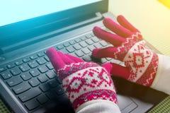 使用膝上型计算机在一个冷的冬天-有手套的女性 免版税库存照片