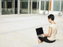使用膝上型计算机在办公室外的女实业家 免版税图库摄影