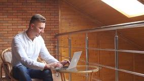 使用膝上型计算机在家客厅家庭办公室的成功的商人,知道好消息的专业男性雇主 股票录像