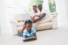 使用膝上型计算机在长沙发和他们的使用片剂的女儿的俏丽的夫妇 库存照片