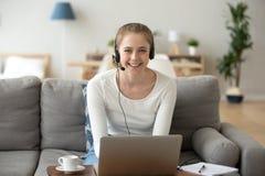 使用膝上型计算机工作或在家学习的女孩佩带的耳机 免版税库存照片