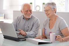 使用膝上型计算机微笑的高级人员 免版税库存图片