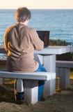 使用膝上型计算机有海视图的人 免版税库存照片