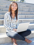 使用膝上型计算机的一个亚裔女孩的画象室外 免版税库存照片