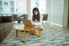 使用膝上型计算机的一个亚裔性感的女商人在图书馆 免版税库存图片