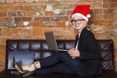 使用膝上型计算机的一个年轻秀丽女商人的画象在办公室在与圣诞老人帽子的新年前 到达天空的企业概念金黄回归键所有权 库存图片