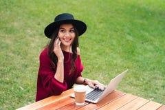 使用膝上型计算机的一个快乐的年轻亚裔女孩的画象 免版税库存照片