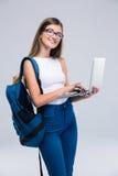 使用膝上型计算机的一个愉快的女性少年的画象 免版税库存图片
