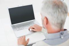 使用膝上型计算机的一个灰发的人的特写镜头背面图在书桌 免版税库存图片