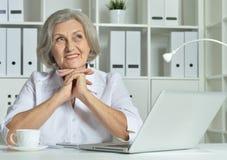 使用膝上型计算机的一个老女商人的画象 免版税库存照片