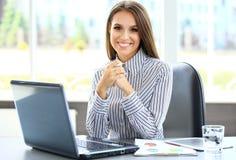使用膝上型计算机的一个年轻女商人的画象 库存照片