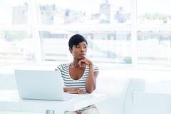 使用膝上型计算机的一名严肃的体贴的女实业家的画象在办公室 免版税库存照片