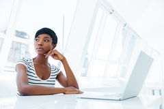 使用膝上型计算机的一名严肃的体贴的女实业家的画象在办公室 免版税库存图片