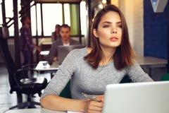 使用膝上型计算机的一名严肃的女实业家的画象在办公室 图库摄影