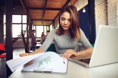 使用膝上型计算机的一名严肃的女实业家的画象在办公室 免版税库存照片