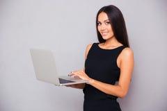 使用膝上型计算机的一名微笑的美丽的妇女的画象 库存照片