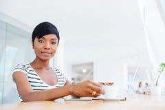 使用膝上型计算机的一名愉快的微笑的非洲女实业家的画象 免版税图库摄影