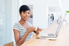 使用膝上型计算机的一名愉快的微笑的非洲女实业家的画象 免版税库存图片