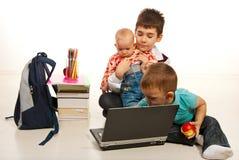使用膝上型计算机的三个兄弟 免版税库存图片