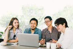 使用膝上型计算机的不同的小组亚裔企业工友或大学生在队偶然会议,起始的项目讨论 免版税库存照片