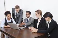 使用膝上型计算机的不同种族的专家在会议室 免版税库存图片