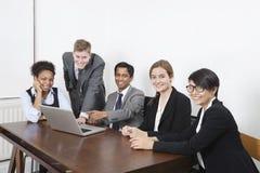 使用膝上型计算机的不同种族的专家画象在会议室 库存照片