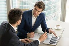 使用膝上型计算机的两个严肃的商人,谈论新的项目在 免版税图库摄影
